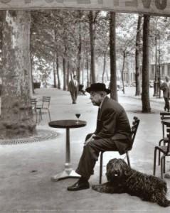 """""""Jacques Prévert assis à la terrasse d'un café avec son chien"""" - Photographie de Robert Doisneau"""